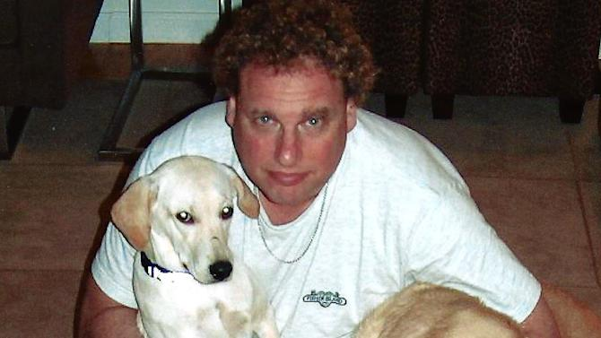 In this undated family handout, New York Yankees president Randy Levine poses with Labrador retrievers. The Westminster dog show begins its two-day run on Monday, Feb. 11, 2013, and warming up in the dogpen is the Bronx Bowser, a Labrador retriever named Mitch (not shown) co-owned by Levine.  (AP Photo/Mindy Levine)