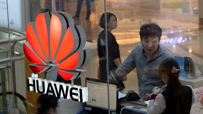 An employee uses a computer as she deals with a customer at a Huawei store in Beijing on March 24, 2014