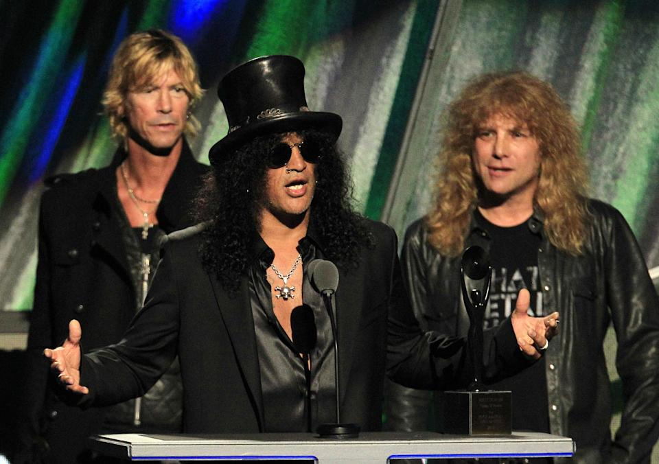 Guitarist Slash gestures with Duff McKagan, back left, and Steven Adler after Guns N' Roses was inducted into the Rock and Roll Hall of Fame Saturday, April 14, 2012, in Cleveland. (AP Photo/Tony Dejak)