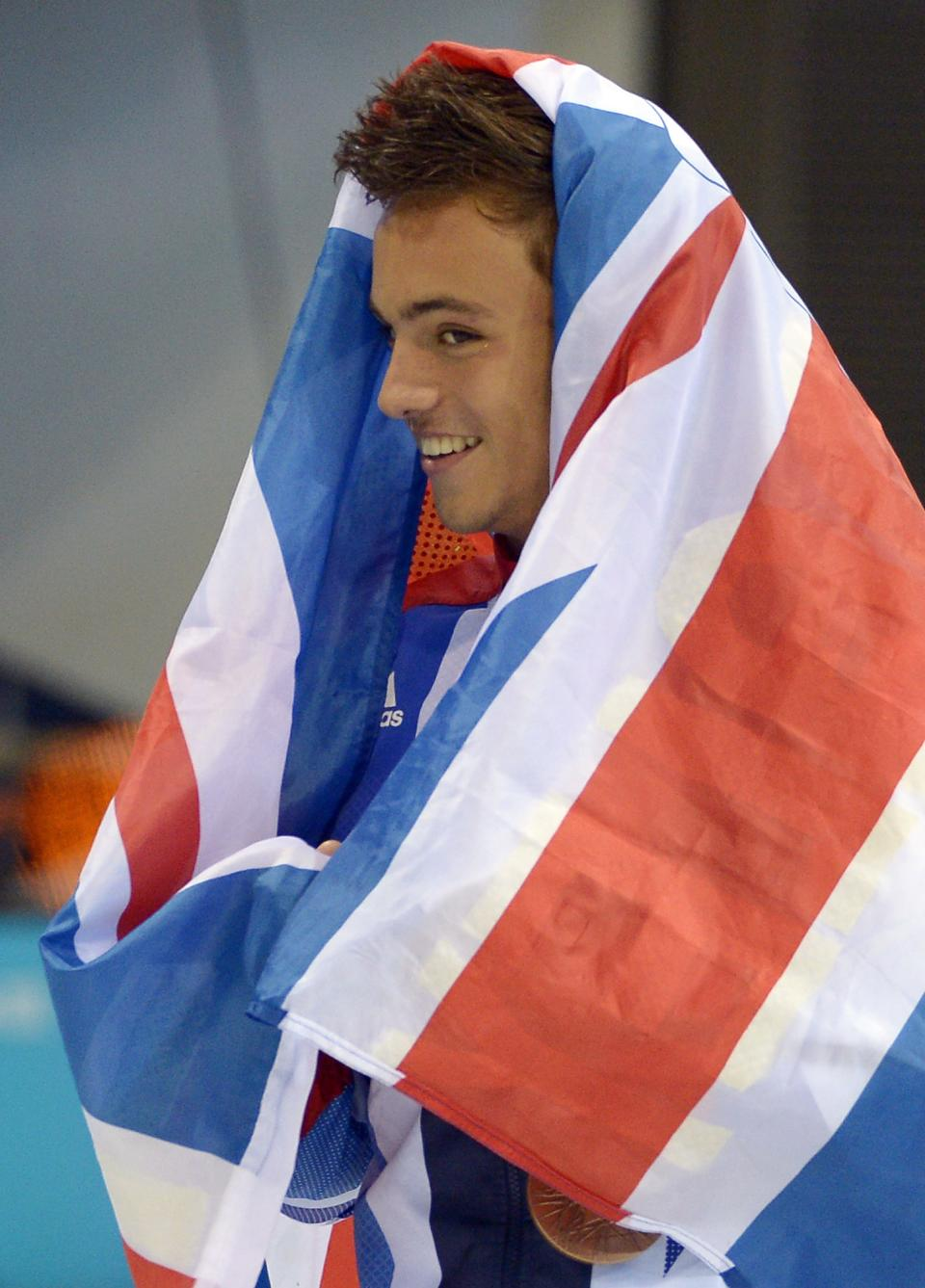 Thomas Daley of Great Britain wraps a flag around himself after the men's 10-meter platform diving final at the Aquatics Centre in the Olympic Park during the 2012 Summer Olympics in London, Saturday, Aug. 11, 2012. Daley won the bronze medal in the event. (AP Photo/Mark J. Terrill)