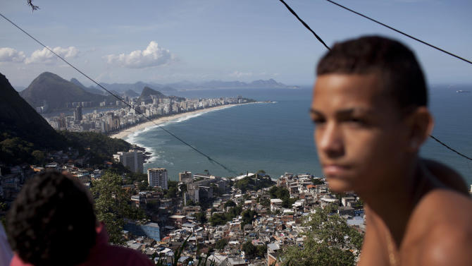 Ipanema beach, top, is seen from the Vidigal shantytown in Rio de Janeiro, Brazil, Tuesday, May 22, 2012. Local officials and human rights groups are working to give legal title to tens of thousands of residents of shantytowns, a process that increases their wealth and gives them greater access to credit, as well as peace of mind. The programs so far are just a start at tackling a widespread problem: A third of the people in Rio state, nearly 5 million people, don't have title to their homes, an uncertainty shared by most of the approximately 1 billion people who living in slums globally. (AP Photo/Felipe Dana)