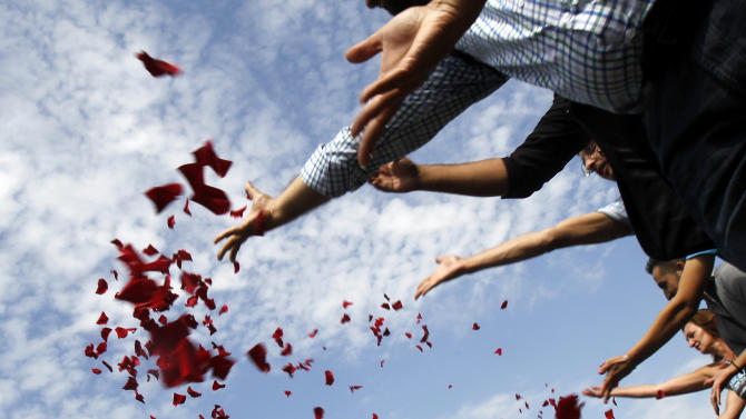 Members of Romania's ethnic Roma minority throw flower petals into Dambovita river during a commemoration ceremony next to the Holocaust Memorial in Bucharest