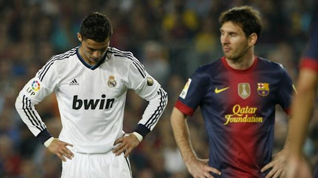 Barcelona&#39;s Lionel Messi (R) walks past Real Madrid&#39;s Cristiano Ronaldo (Reuters)