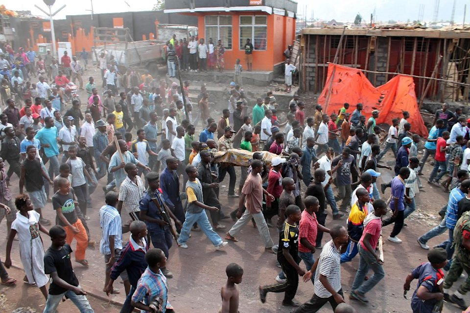 Angry residents carry the body of a person killed hours earlier when a rocket struck a home, as they take to the streets in protest over recent violence, in Goma, Congo, Saturday, Aug. 24, 2013. Congolese soldiers supported by U.N. forces fought rebels in the country's deteriorating east for hours early Saturday, officials said, while a rocket landed inside the town of Goma. Congo immediately blamed the attacks on neighboring Rwanda, which has long been accused of supporting the eastern Congolese rebel movement known as M23. (AP Photo/Alain Wandimoyi)