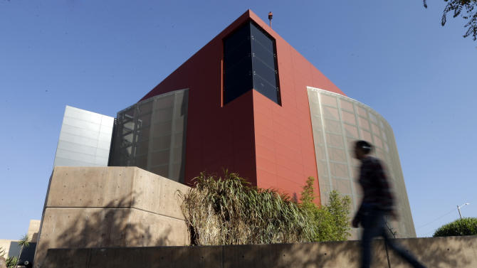 "In this Friday, Dec. 7, 2012 photo, a man walks past an expansion of the Tijuana Cultural Center known as ""The Cube,"" designed by architect Eugenio Velazquez, in Tijuana, Mexico. Velazquez doesn't fit the mold of the down-on-his luck, uneducated, underemployed courier who ferries drugs to the United States for Mexican drug cartels. Yet, now he awaits sentencing in San Diego for concealing 12.8 pounds of cocaine while entering the U.S. (AP Photo/Gregory Bull)"