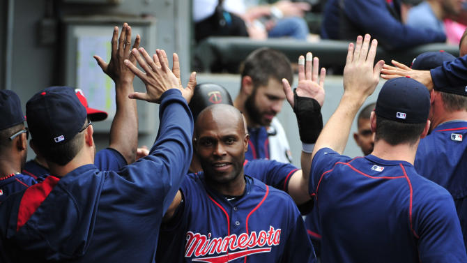 Minnesota Twins' Torii Hunter, center, is greeted by his teammates after scoring on a Eddie Rosario single against the Chicago White Sox during the fourth inning of a baseball game, Sunday, May 24, 2015 in Chicago.  (AP Photo/David Banks)