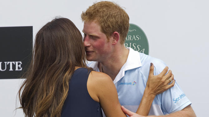 Britain's Prince Harry greets Brazilian model Fernanda Motta during an award ceremony after playing a charity polo match in Campinas, Brazil, Sunday March 11, 2012.  Prince Harry is in Brazil at the request of the British government on a trip to promote ties and emphasize the transition from the upcoming 2012 London Games to the 2016 Olympics in Rio de Janeiro. (AP Photo/Andre Penner)