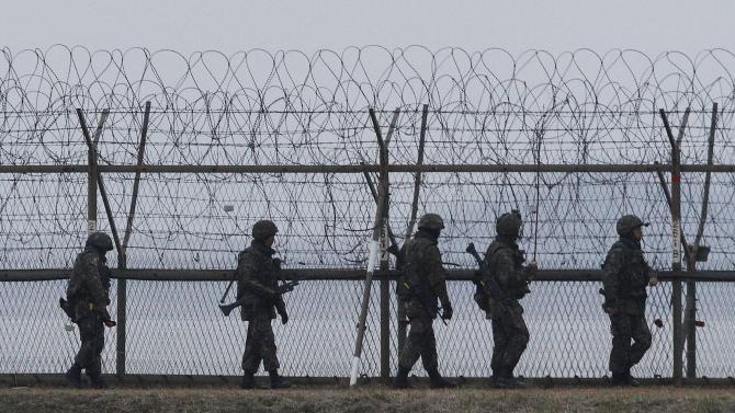South Korean army soldiers patrol along a barbed-wire fence near the border village of the Panmunjom, in Paju, South Korea, Monday, April 8, 2013. North Korea said Monday it will recall 51,000 North Korean workers and suspend operations at a factory complex it has jointly run with South Korea, moving closer to severing its last economic link with its rival as tensions escalate. (AP Photo/Ahn Yong-joon)