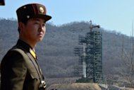 A soldier stands guard in front of the Unha-3 rocket at North Korea's Tangachai-ri space center in April. North Korea has installed the first stage of a long-range rocket it plans to launch this month in position, a report said Monday