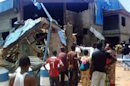 Bystanders look at the Sharon Church after it was struck by a suicide bomber in Kaduna