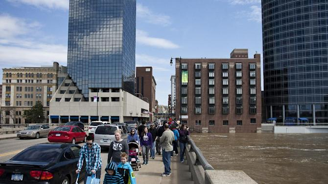 Crowds of people check out the level of the Grand River in downtown Grand Rapids, Mich., Sunday, April 21, 2013. The rising Grand River has driven hundreds of people from their homes in several western Michigan communities and was pushing Sunday toward a record high near Grand Rapids. (AP Photo/MLive.com, Sally Finneran)