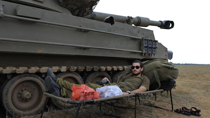 An Israeli soldier rests next to a mobile artillery vehicle at a staging area near the Israel Gaza Strip Border, southern Israel, Thursday, Nov. 22, 2012. A cease-fire agreement between Israel and the Gaza Strip's Hamas rulers took effect Wednesday night, bringing an end to eight days of the fiercest fighting in years and possibly signaling a new era of relations between the bitter enemies. (AP Photo/Tsafrir Abayov)