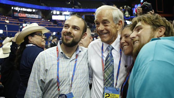 FILE - In this Aug. 28, 2012, file photo, Rep. Ron Paul, R-Texas, poses with Texas delegates on the floor at the Republican National Convention in Tampa, Fla. At least three Republican electors say they may not support their party's presidential ticket when the Electoral College meets in December to formally elect the new president. That prospect is escalating tensions within the GOP and adding a fresh layer of intrigue to the final weeks of the White House race. (AP Photo/Jae C. Hong, File)