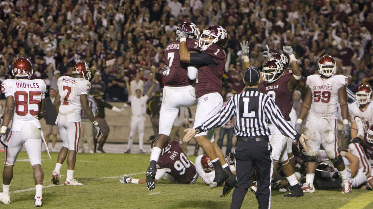 Texas A&M defensive players Terrence Federick (7) and Trent Hunter (1) celebrate after stopping Oklahoma just short of the end zone during the fourth quarter of an NCAA college football game in College Station, Texas, Saturday, Nov. 6, 2010. Texas A&M won 33-19. (AP Photo/Steve Campbell)