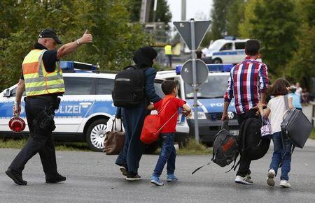 A German policeman directs migrants towards a registration point after crossing the border from Austria in Freilassing