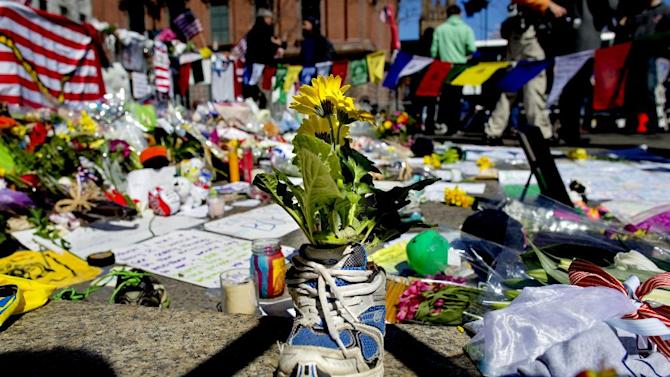 FILE - A memento of flowers in a running shoe rests at a makeshift memorial in Boston's Back Bay neighborhood on Thursday, April 18, 2013, a few blocks from the finish line of the Boston Marathon. (AP Photo/Craig Ruttle)