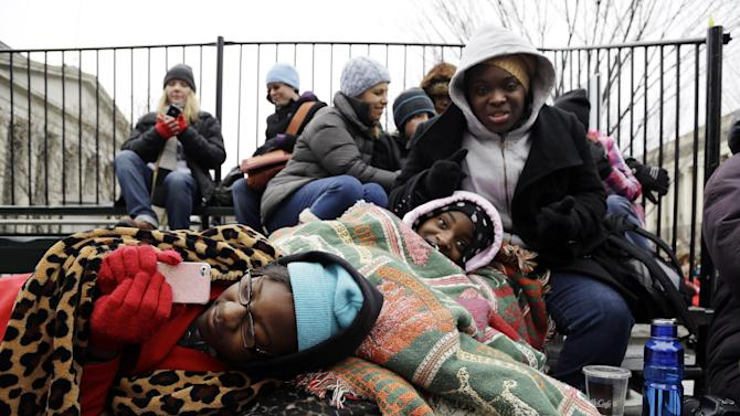 Afrika Lewis, left, and Ausja Mason, center, of Birmingham, Ala., watch the Inaugural ceremonies on a smart phone Monday, Jan. 21, 2013, in Washington. (AP Photo/Steve Helber)