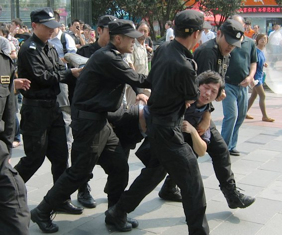 Chinese police officers carry a demonstrator away while people protest the proposed expansion of a petrochemical factory that they say would spew pollution and damage public health, in Ningbo, Zhejiang province, China Saturday, Oct. 27, 2012. Pollution has become a major source of unrest in China, as members of the rising middle class become more outspoken against environmentally risky projects in their backyards. (AP Photo/Kyodo News) JAPAN OUT, MANDATORY CREDIT, NO LICENSING IN CHINA, FRANCE, HONG KONG, JAPAN AND SOUTH KOREA