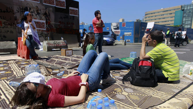 Protesters stage a sit-in on a street near the parliament building in Beirut, Lebanon, Friday, June 21, 2013. A group of protesters stayed overnight to protest against the 128-member parliament that extended its term by a year and a half last month, skipping scheduled elections because of deteriorating security conditions in the country related to the war in Syria. (AP Photo/Bilal Hussein)
