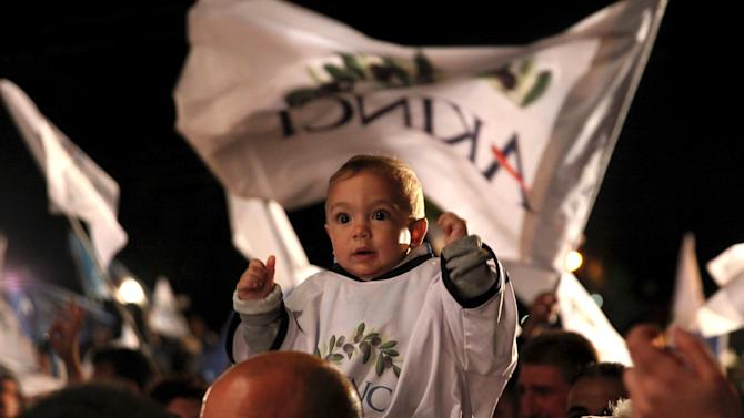 A man carries a child during celebrations after an election victory in Nicosia