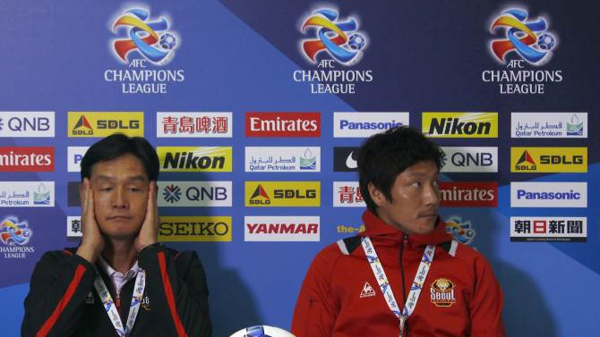 Choi, coach of FC Seoul soccer team, reacts as he sits down next to team captain Kim at the start of a media conference at Parramatta Stadium