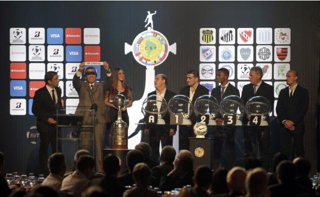 Juan Angel Napout, President of the Paraguayan Football Association, holds up a piece of paper with the name of Peru's soccer team Sporting Cristal during the draw for the 2014 Copa Libertadores i