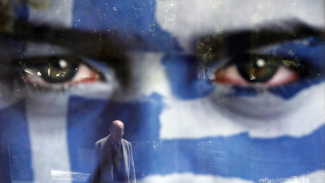 A pedestrian is reflected on an election poster of Democratic Alliance party at a bus stop in Athens, Saturday May 5 2012. Greeks head to the polls Sunday in their most critical and uncertain  election in decades, with voters set to punish the two main parties that are being held responsible for the country's dire economic straits. (AP Photo/Kostas Tsironis)