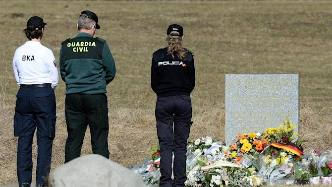 German and Spanish police officers pay tribute to the victims of the Germanwings plane crash at a memorial in Le Vernet on March 27, 2015