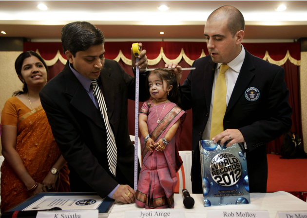 Guinness World Records adjudicator Rob Molloy, right, and Dr. Manoj Pahukar of Wockhardt hospital, second left, measure Jyoti Amge at a press conference in Nagpur, India, Friday, Dec. 16, 2011. Amge,
