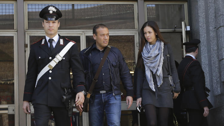 Karima el-Mahroug's, right, flanked by her husband Luca Risso, is escorted outside the Milan's Law court by a Carabinieri police officer after giving her testimony at the trial of three former Berlusconi aides accused with procuring her and other woman for prostitution, in Milan, Italy, Friday, May 17, 2013. Silvio Berlusconi's private disco featured not only aspiring show girls performing striptease acts as sexy nuns and nurses, but also dressed as President Barack Obama and a prominent Milan prosecutor whom the billionaire media mogul has accused of persecuting him, according to the first public sworn testimony by the Moroccan woman at the center of the scandal. (AP Photo/Luca Bruno)