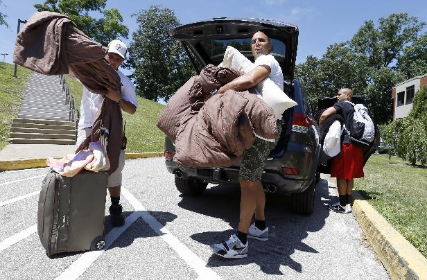 Pittsburgh Steelers backup quarterback Bruce Gradkowski, center, gets some help unloading his vehicle as he arrives for NFL football training camp at the team training facility in Latrobe, Pa., on Friday, July 25, 2014. (AP Photo)