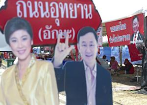 Pro-government 'Red shirts' sit next to portraits…