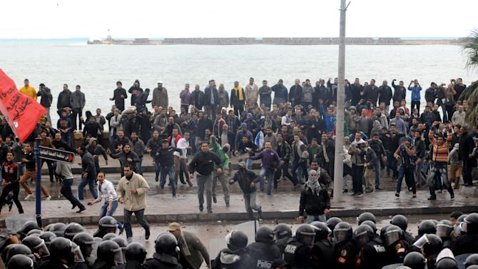 Opponents of Egyptian President Mohammed Morsi clash with Islamist supporters of the president, unseen, as a cordon of riot police separates the groups in Alexandria, Egypt, Friday, Dec. 21, 2012. Thousands of Islamists clashed with their opponents Friday in Egypt's second largest city, Alexandria, on the eve of the second leg of voting on the country's contentious constitution that has deeply polarized the nation.(AP Photo)