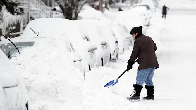 Tina Khoshaboo clears snow from her car on South Water Street during the aftermath of a blizzard in the Byram section of Greenwich, Conn., Saturday morning, Feb. 9, 2013. (AP Photo/Greenwich Time, Bob Luckey)  MANDATORY CREDIT; MAGS OUT