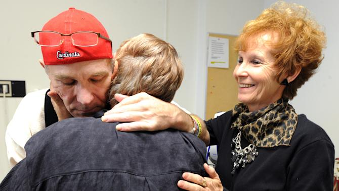 FILE - In this Oct. 3, 2011 file photo, Mark Lindquist, of Joplin, Mo., is embraced by his sisters Vehrlene Crosswhite, left, and Linda Baldwin just before being released from the Missouri Rehabilitation Center in Mount Vernon, Mo. By all accounts, Lindquist is a hero, an underpaid social worker who nearly gave his life trying to save three developmentally disabled adults from the Joplin tornado. But heroism doesn't pay the bills, not when the tornado's 200 mph winds tossed Lindquist nearly a block, broke every rib, obliterated his shoulder, knocked out most of his teeth and put him in a coma for three months. (AP Photo/The Joplin Globe, T. Rob Brown, File)