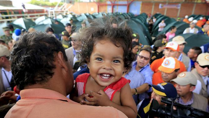 Colombian girl, who was deported with her family from Venezuela, smiles for the camera during the visit of Colombian President Santos at a temporary shelter in Villa del Rosario, Colombia