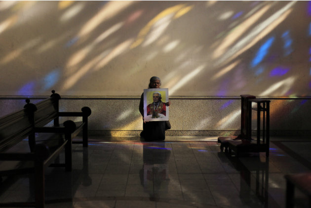 Adelina Hidalgo holds a photograph of Pope Benedict as she kneels inside the Metropolitan Cathedral in San Salvador