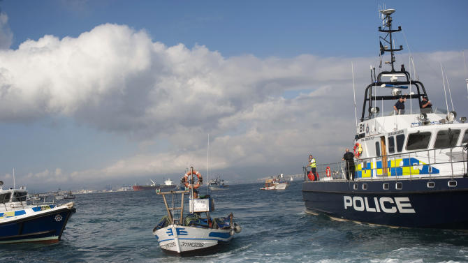 British patrol boats, left and right, block access as a fisherman on his fishing boat, center, protests near to La Linea de la Concepcion in front of Gibraltar, Spain, Sunday, Aug. 18, 2013. Spanish fishermen in some 60 fishing boats are protesting the building of an artificial reef near the disputed British territory of Gibraltar, which has also soured relations between Madrid and London. The fishermen say the reef of around 70 concrete blocks, some with steel rods protruding, can snare their nets. (AP Photo/Laura Leon)