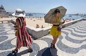 A tourist uses an umbrella to protect from the sun…