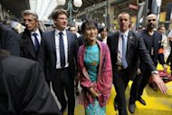 Myanmar pro-democracy leader Aung San Suu Kyi (C) is surrounded by Pascal Canfin (2nd L) , French Minister Delegate for Development as she arrives at the train station gare du Nord in Paris
