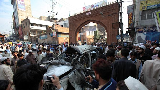 People gather around a destroyed vehicle targeted by attackers in Peshawar, Pakistan, Wednesday, Nov. 7, 2012. A suicide bombing in northwest Pakistan has killed many people and left more than a dozen injured, police said. (AP Photo/Mohammad Sajjad)