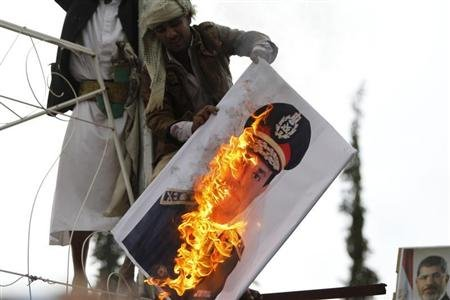 A pro-democracy protester burn image of Lieutenant- General El Sisi during demonstration against what they said was a military coup that ousted Egyptian President Mohamed Mursi, in Sanaa