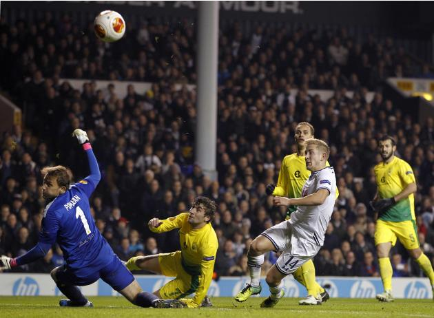Tottenham Hotspur's Lewis Holtby scores the third goal over the head of Anzhi Makhachkala's goalkeeper Evgeni Pomazan and Kamil Agalarov during their Europa League soccer match in London