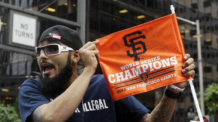 San Francisco Giants pitcher Sergio Romo holds up a flag during the baseball team's World Series victory parade, Wednesday, Oct. 31, 2012, in San Francisco. (AP Photo/Jeff Chiu)