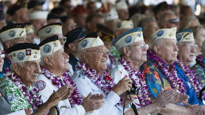 Pearl Harbor survivors watch a vintage WWII airplane fly over Pearl Harbor at the ceremony commemorating the 72nd anniversary of the attack on Pearl Harbor, Saturday, Dec. 7, 2013, in Honolulu. (AP Photo/Marco Garcia)