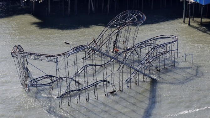 """FILE - In this Friday, Nov. 9, 2012 file photograph, the roller coaster from an amusement pier rests in the Atlantic Ocean in Seaside Heights, N.J., after the region was pounded by Superstorm Sandy. The remains of the roller coaster that was knocked off a New Jersey amusement pier by Superstorm Sandy and partially submerged in the Atlantic Ocean might be left there as a tourist attraction. Seaside Heights Mayor Bill Akers tells WNBC-TV in New York that officials have not made a decision on whether to tear down the coaster. But the mayor says he's working with the Coast Guard to see if the coaster is stable enough to leave it alone because he believes it would make """"a great tourist attraction."""" (AP Photo/Mel Evans)"""