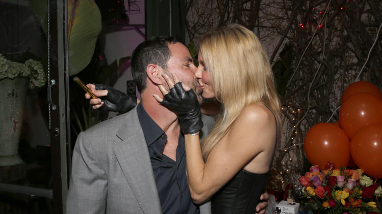 Brandi Glanville (right) kisses Darin Harvey at Darin's 50th Birthday Party at Sur Restaurant, on Saturday March 30, 2013 in Los Angeles.(Photo by Todd Williamson/Invision/AP)