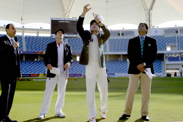 Pakistan captain Misbah-ul-Haq, second right, performs the coin toss watched by England captain Andrew Strauss, second left, television commentator and former England captain Nasser Hussain, left, and