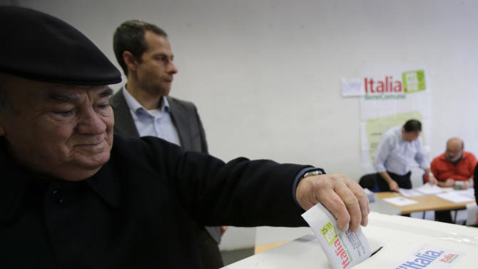 """A man casts his vote during a primary runoff, in Piacenza, Italy, Sunday, Dec. 2, 2012. Italians are choosing a center-left candidate for premier for elections early next year, an important primary runoff given the main party is ahead in the polls against a center-right camp in utter chaos over whether Silvio Berlusconi will run again. Sunday's runoff pits veteran center-left leader Pier Luigi Bersani, 61, against the 37-year-old mayor of Florence, Matteo Renzi, not shown, who has campaigned on an Obama-style """"Let's change Italy now"""" mantra. (AP Photo/Antonio Calanni)"""