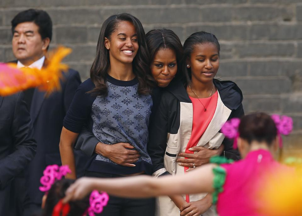 U.S. first lady Michelle Obama hugs her daughters Malia and Sasha as they watch a folk dance by performers during her visit at the City Wall, in Xi...